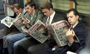 Men reading the Sun on the tube train